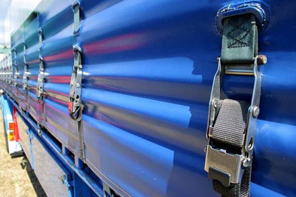 Detail of a load strap on a tautliner truck curtain wall looking along the truck towards the cabin